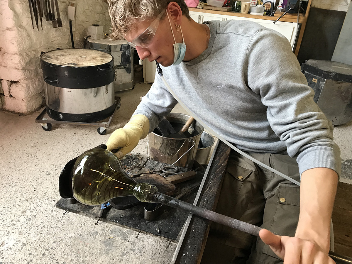 Peter Dupont Is Blowing Into Hot Glass Sitting At The Bench