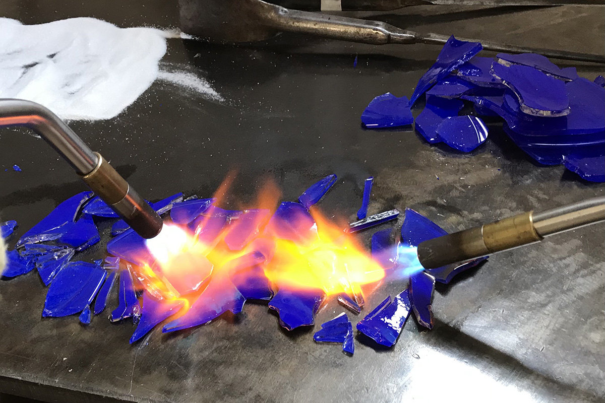 Using Torches To Heat Blue Broken Glass On The Marver
